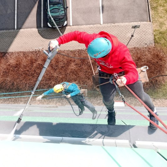 Horolezci čistí plášť budovy tlakovou vodou