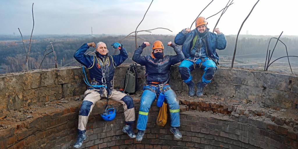 Tři horolezci sedí na komíně