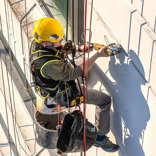 Horolezec natírá spáru mezi panely
