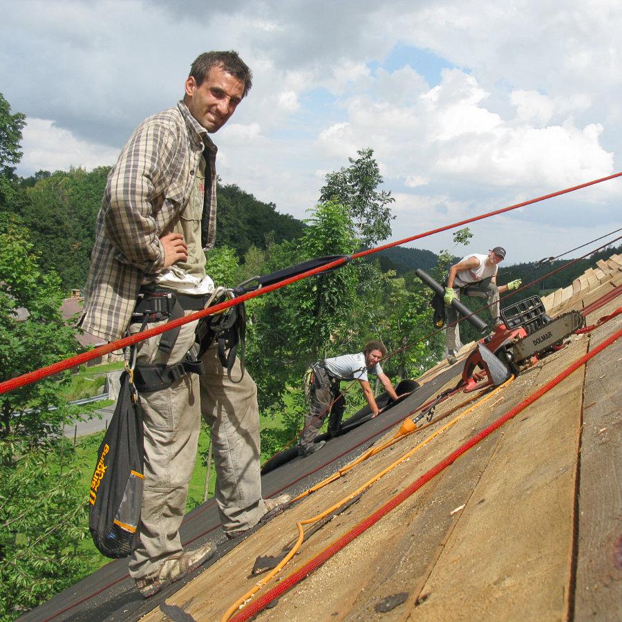 Tři muži opravují střechu